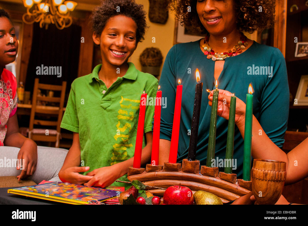 Family lighting kinara candles, celebrating Kwanzaa - Stock Image