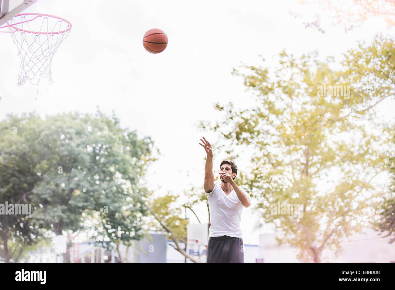 Young male basketball player throwing ball towards basketball net - Stock Image