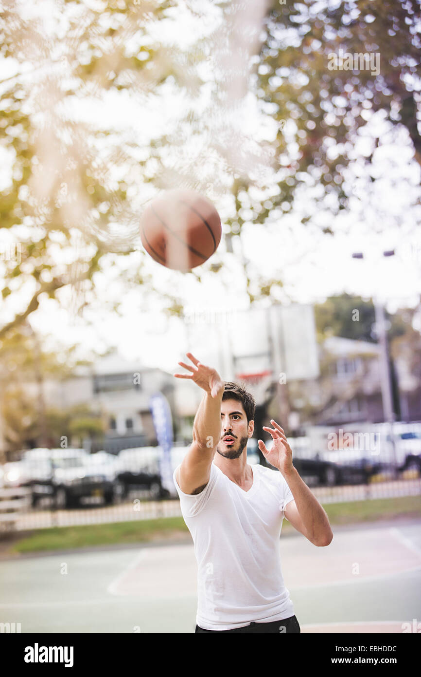 Young male basketball player throwing ball to basketball hoop - Stock Image