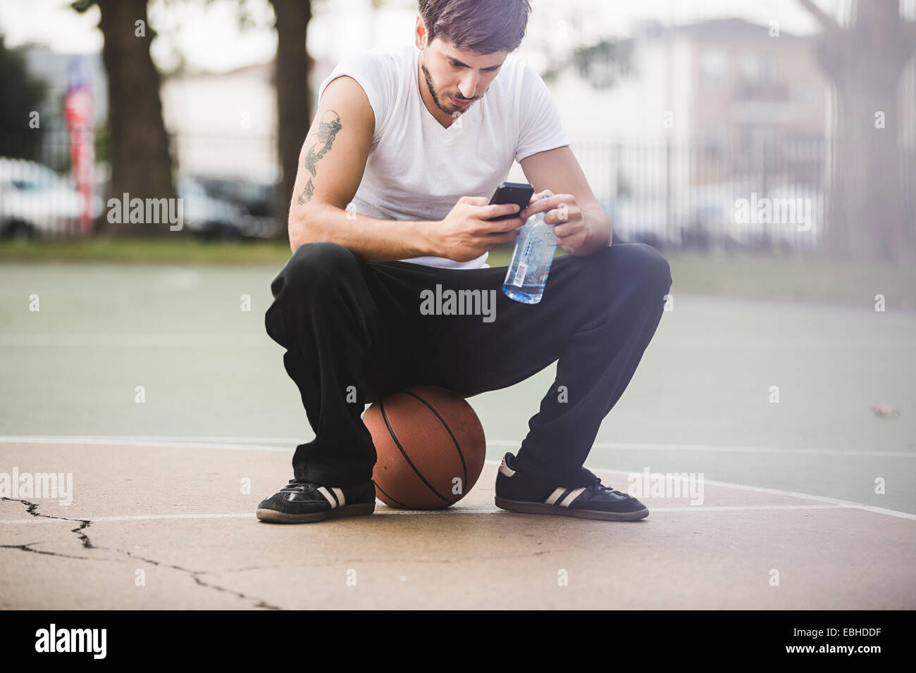 Young male basketball sitting on ball texting on smartphone - Stock Image