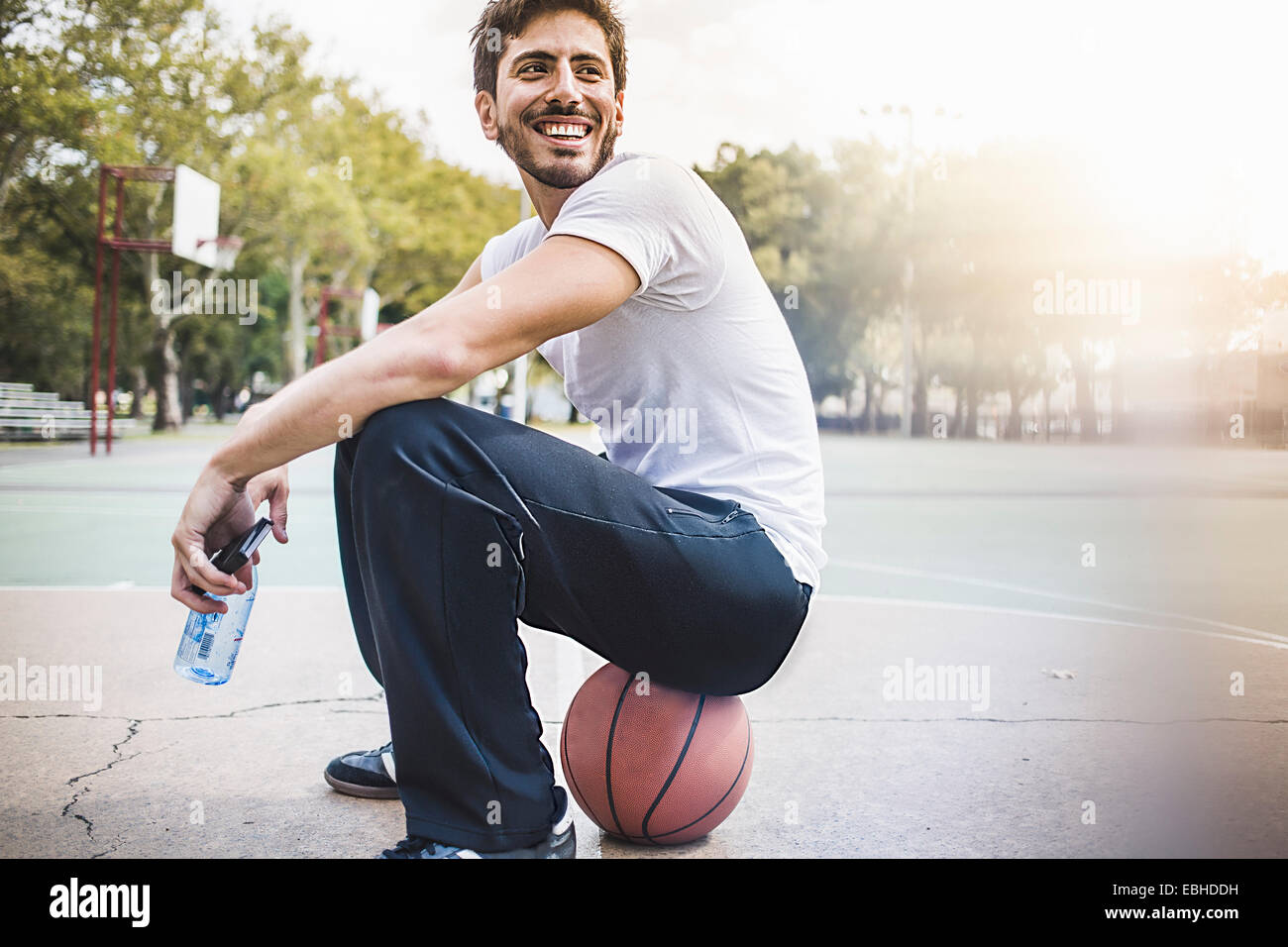 Portrait of young male basketball sitting on ball - Stock Image