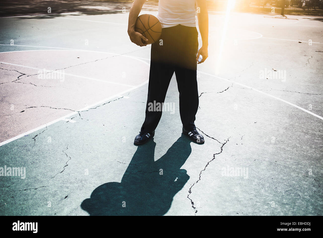 Neck down view of young male basketball holding ball - Stock Image