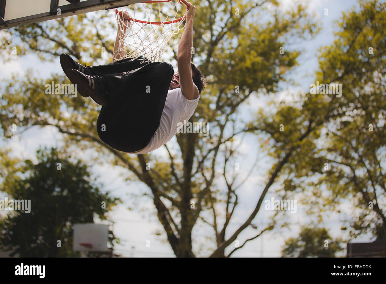 Low angle view of young male basketball hanging from basketball hoop - Stock Image