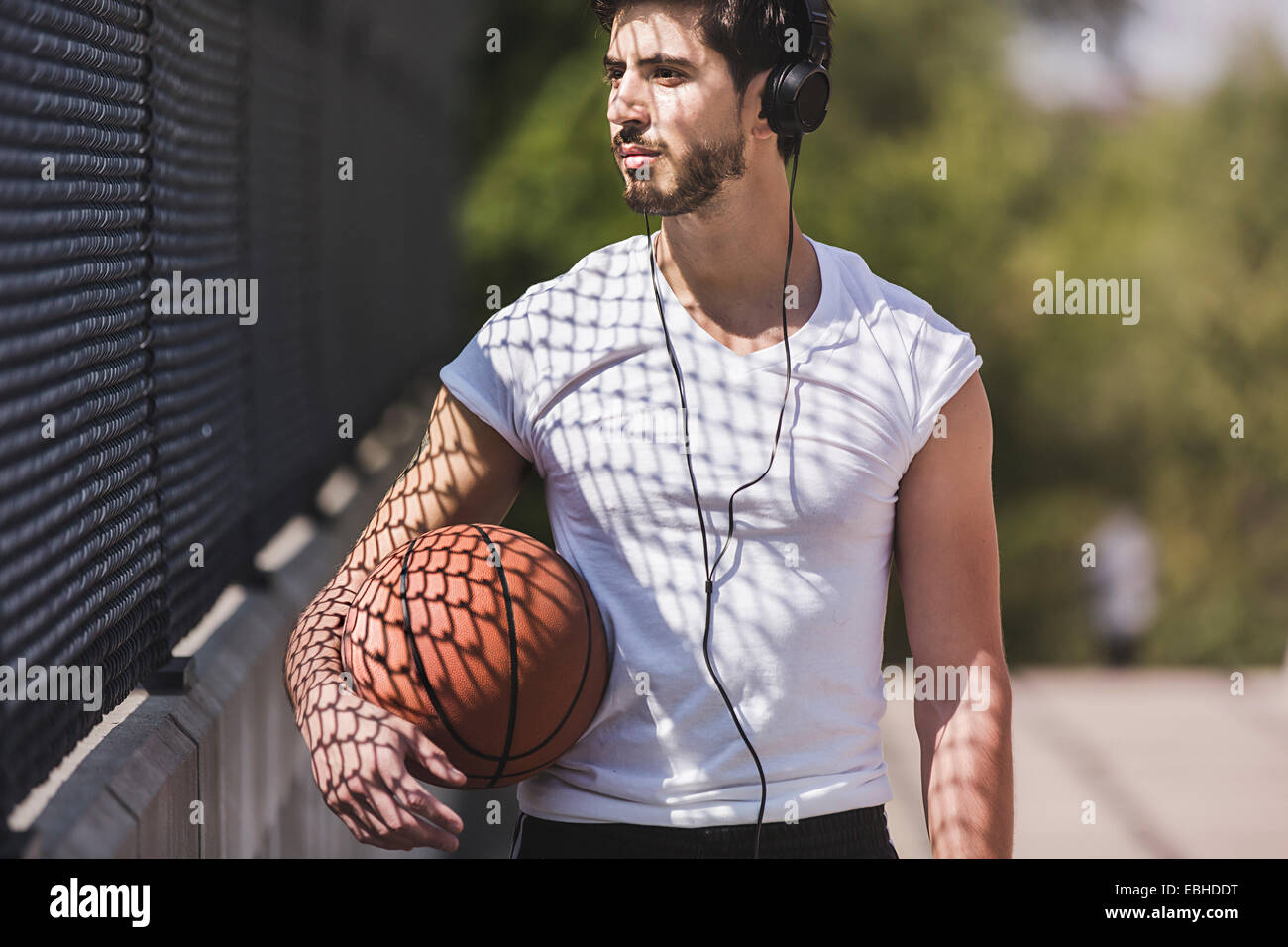 Young male basketball player walking over footbridge listening to headphones - Stock Image