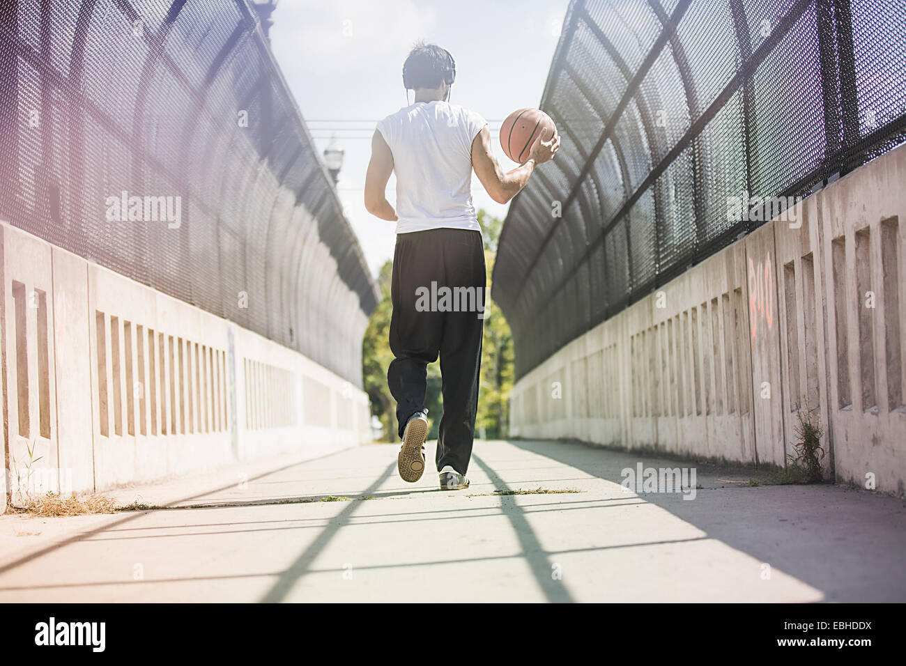 Rear view of young male basketball player walking along footbridge carrying ball - Stock Image