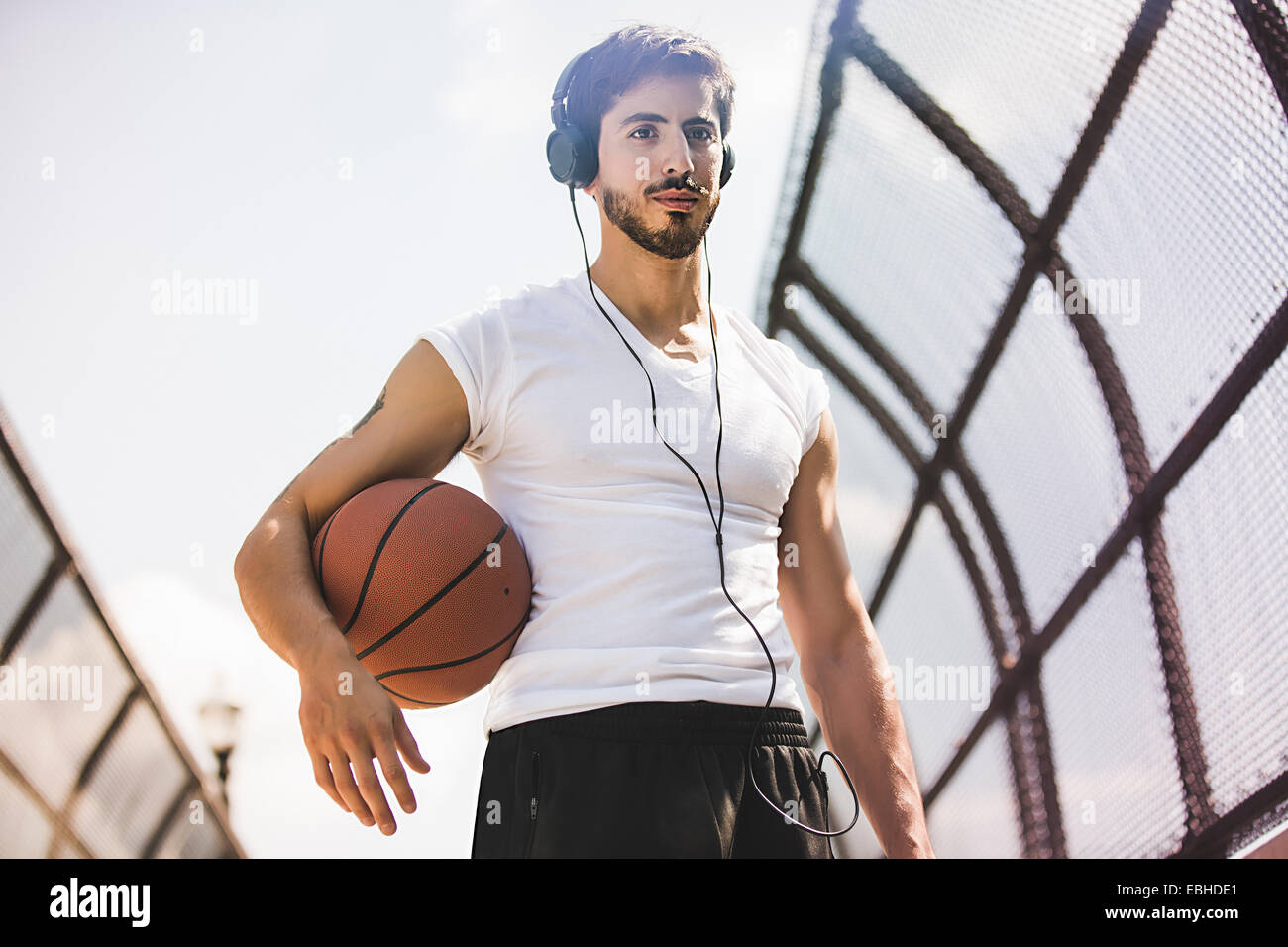 Young male basketball player walking along footbridge listening to headphones - Stock Image