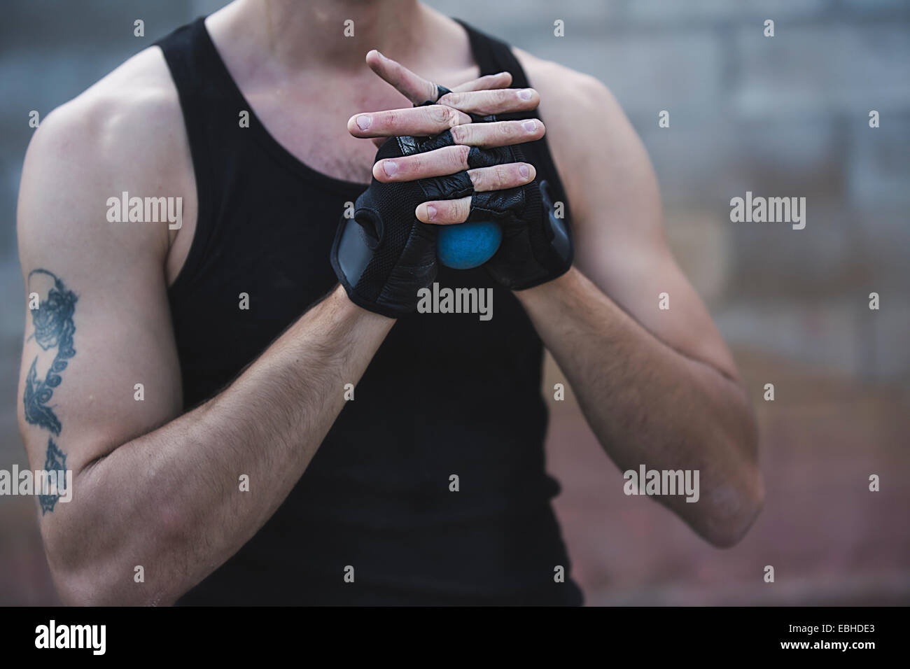Cropped shot of young male handball player squeezing ball - Stock Image