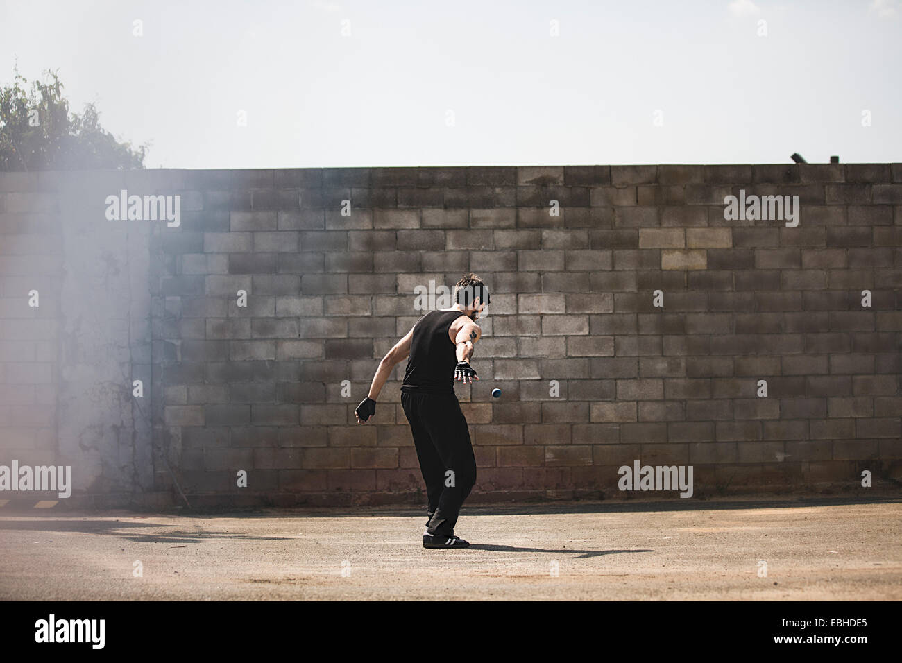 Rear view of young male handball player hitting ball against wall - Stock Image