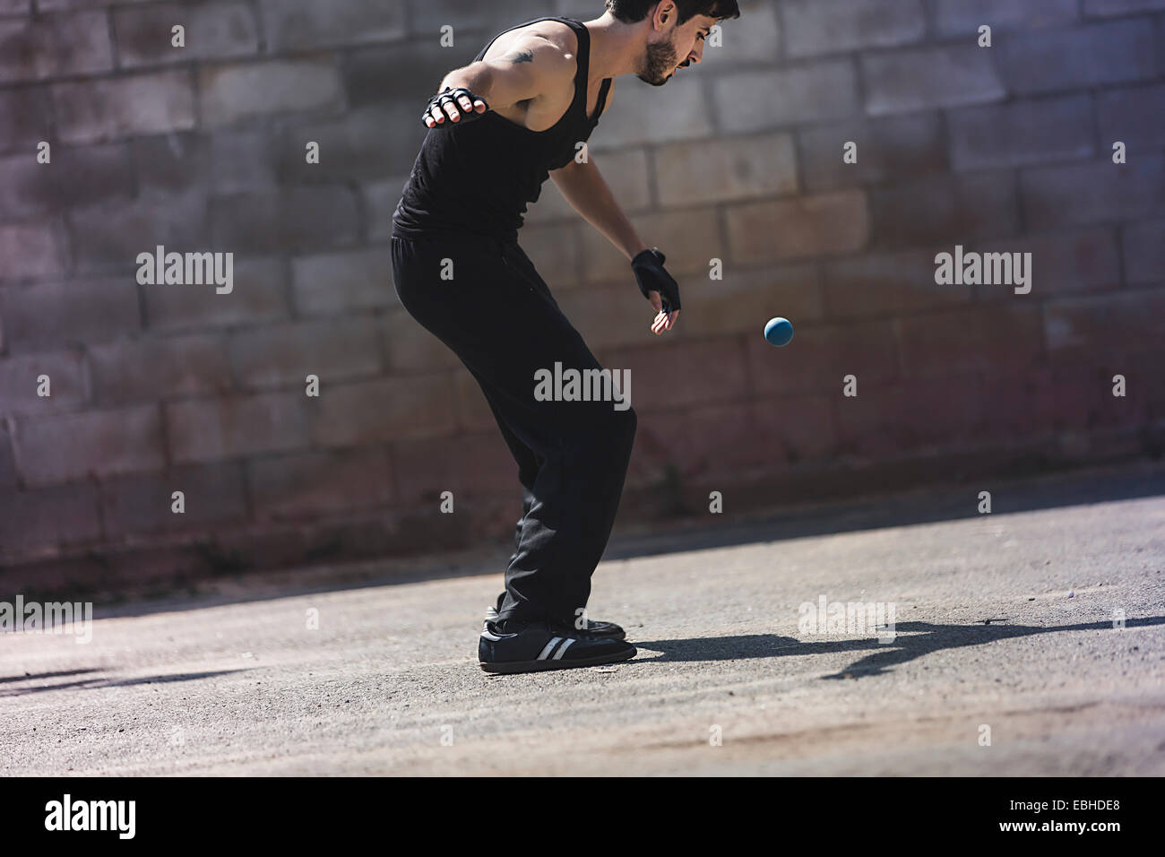 Young male handball player hitting ball against wall - Stock Image