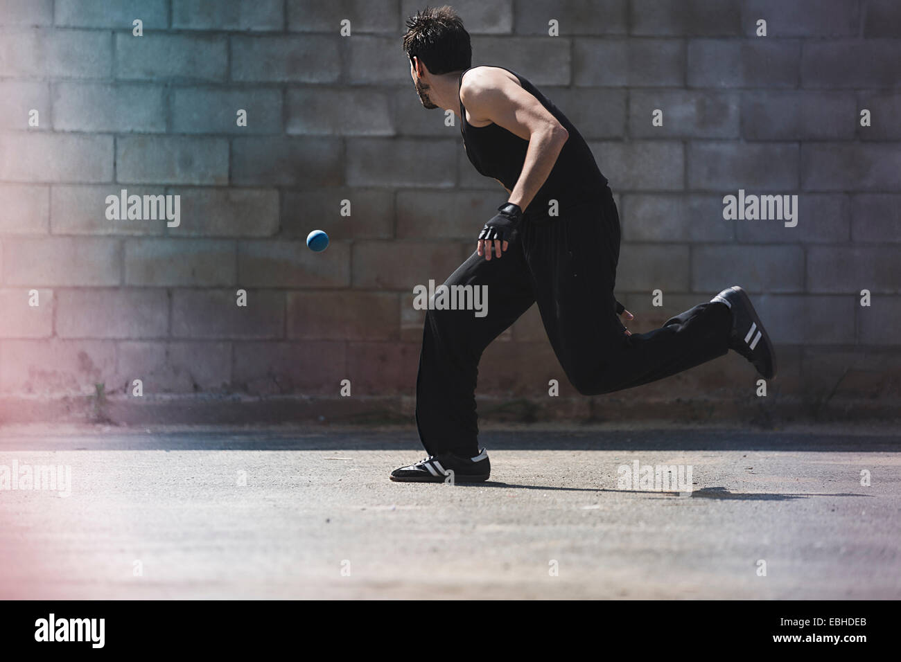 Young male handball player running for ball - Stock Image