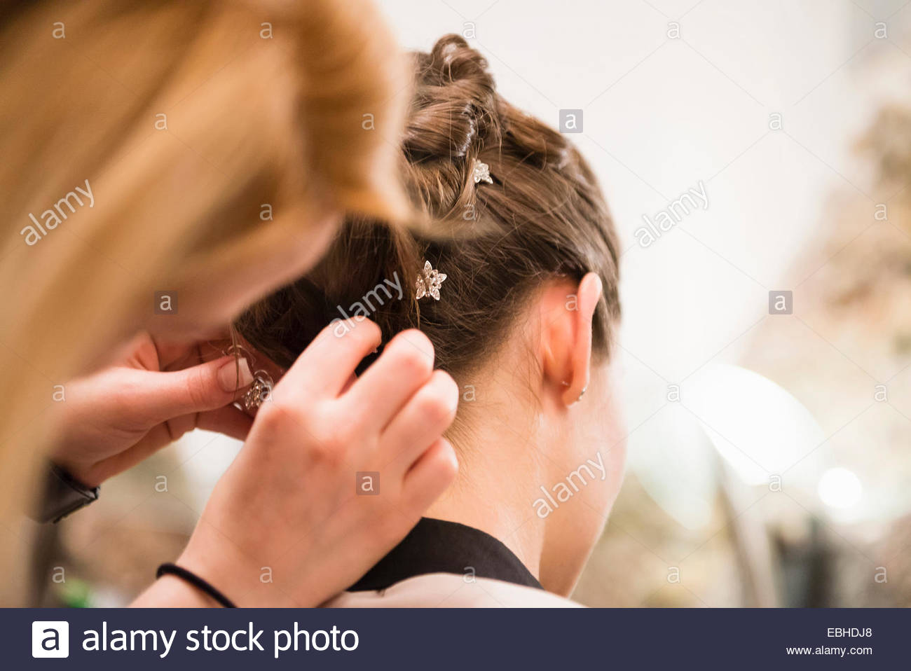 Close up of woman placing hair decoration into brides hair - Stock Image