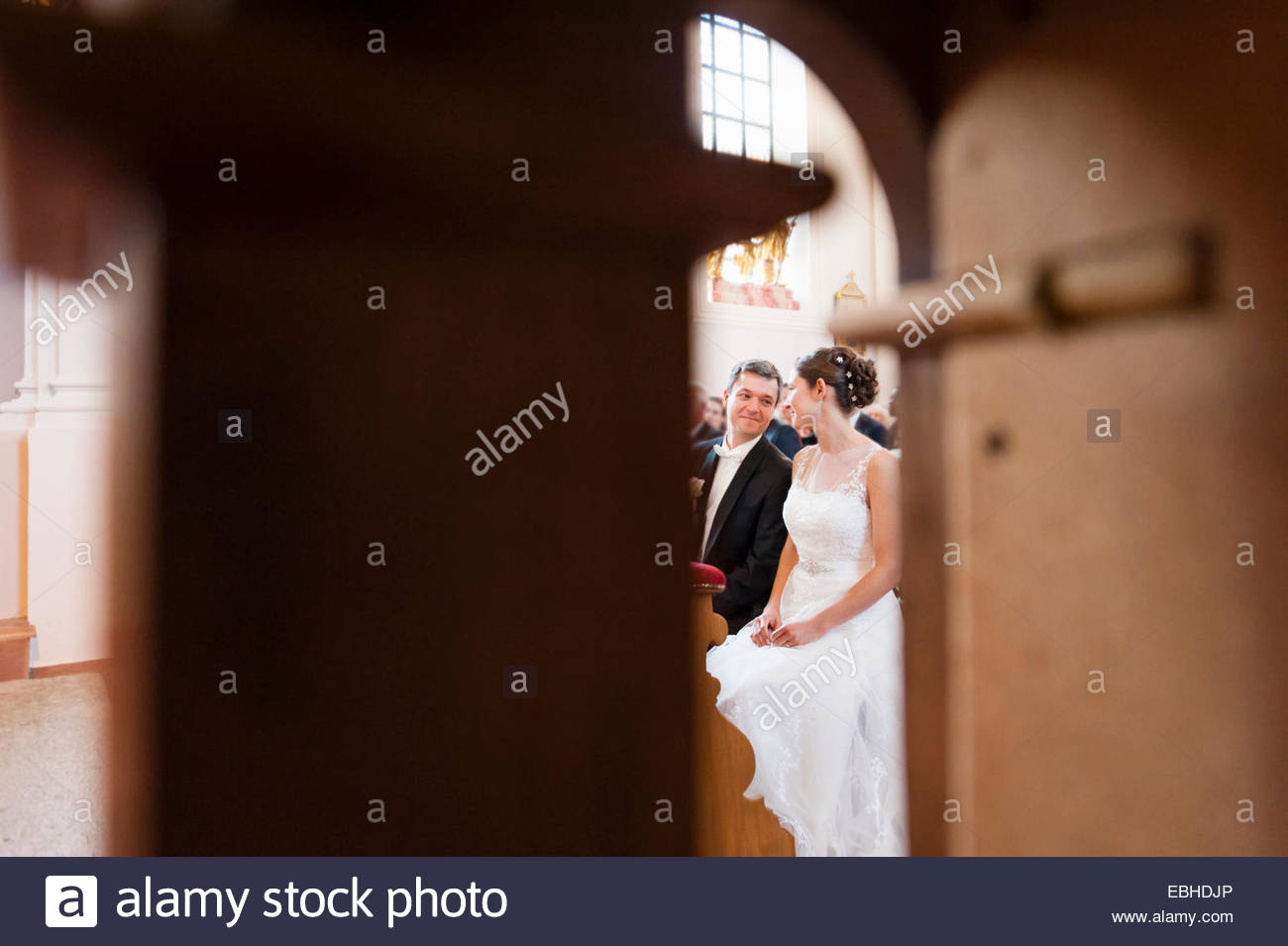 Bride and bridegroom sitting on church pew - Stock Image