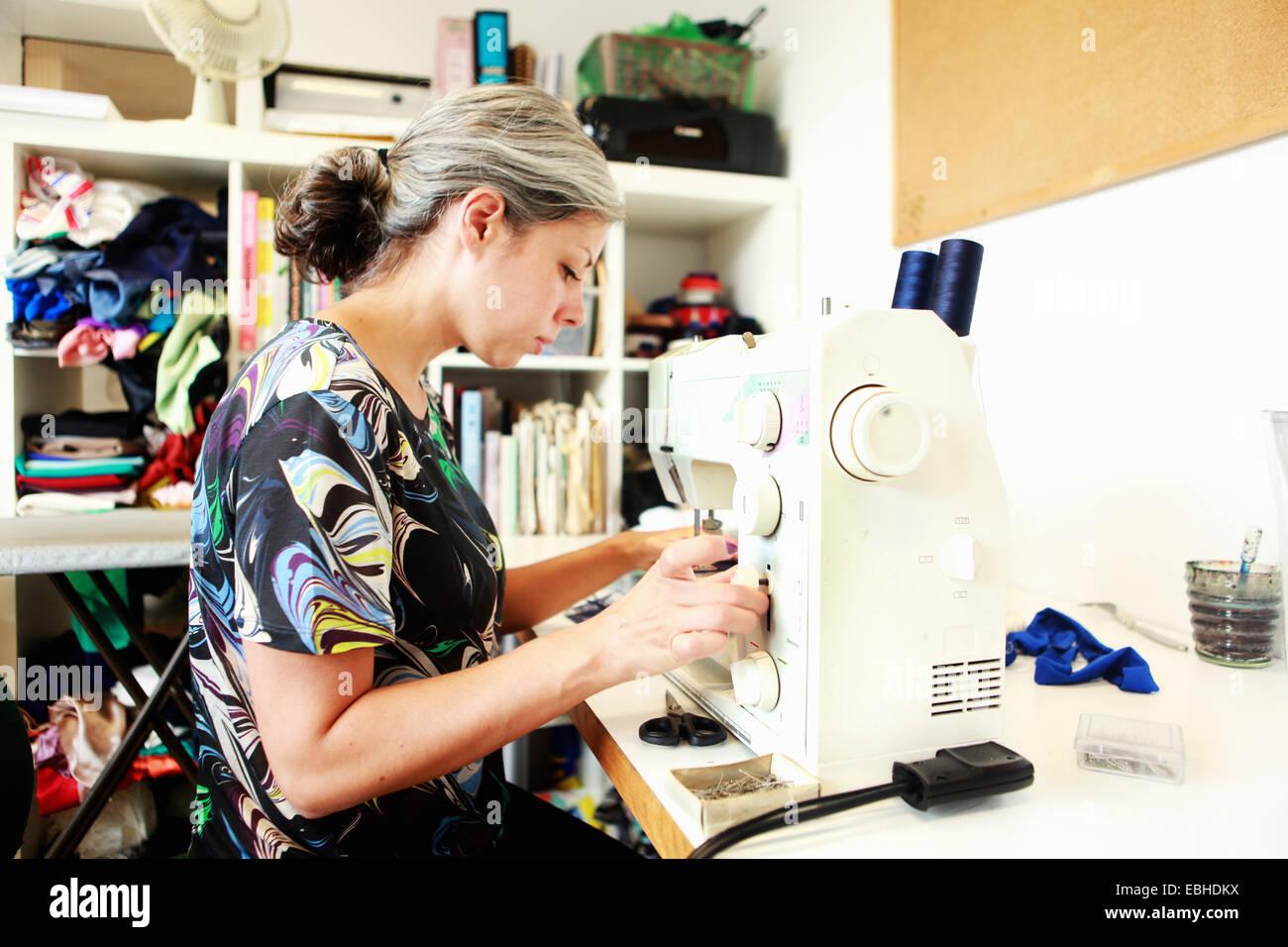 Designer working at sewing machine in studio Stock Photo