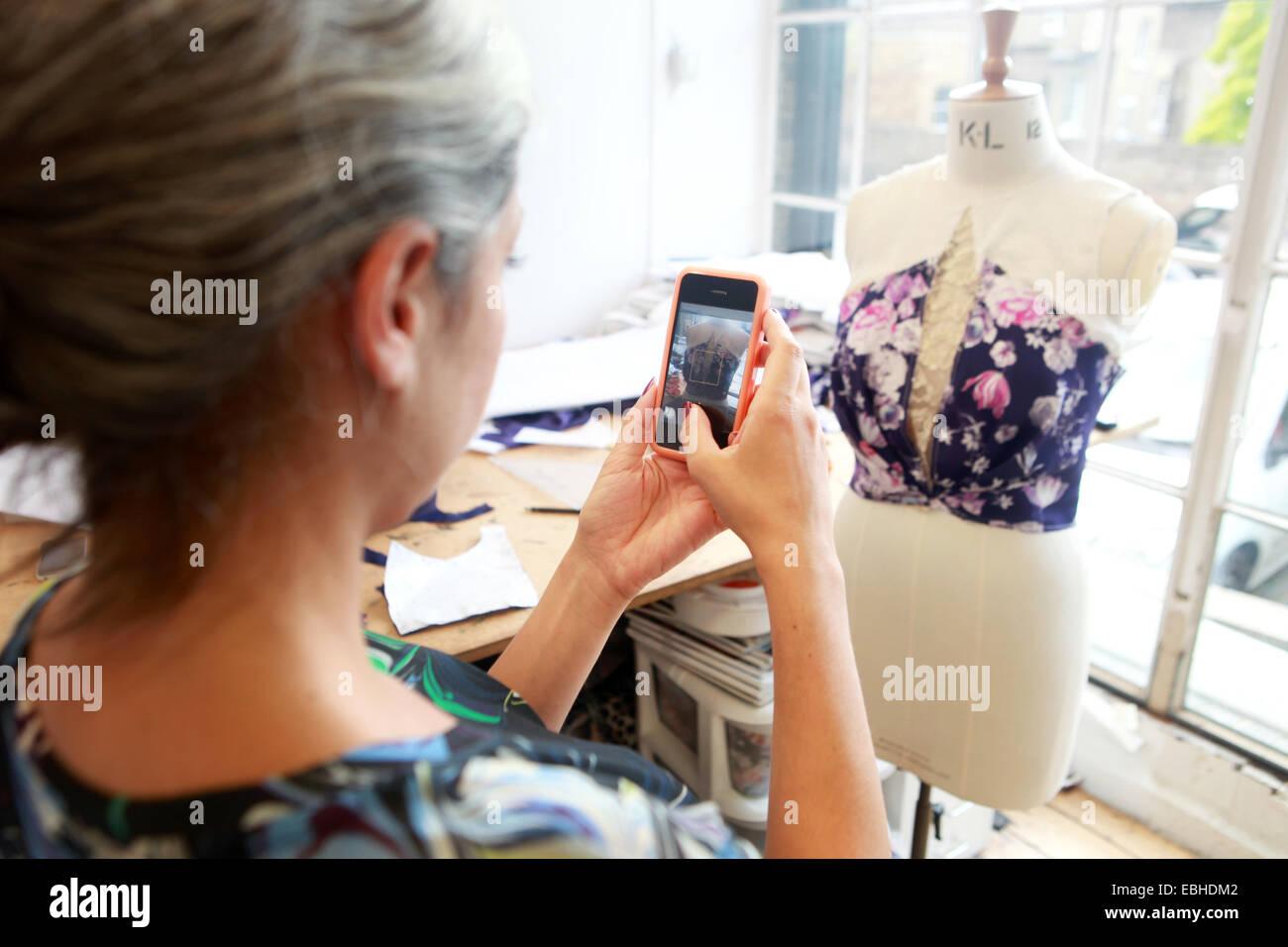 Designer taking photograph of her creation in studio - Stock Image