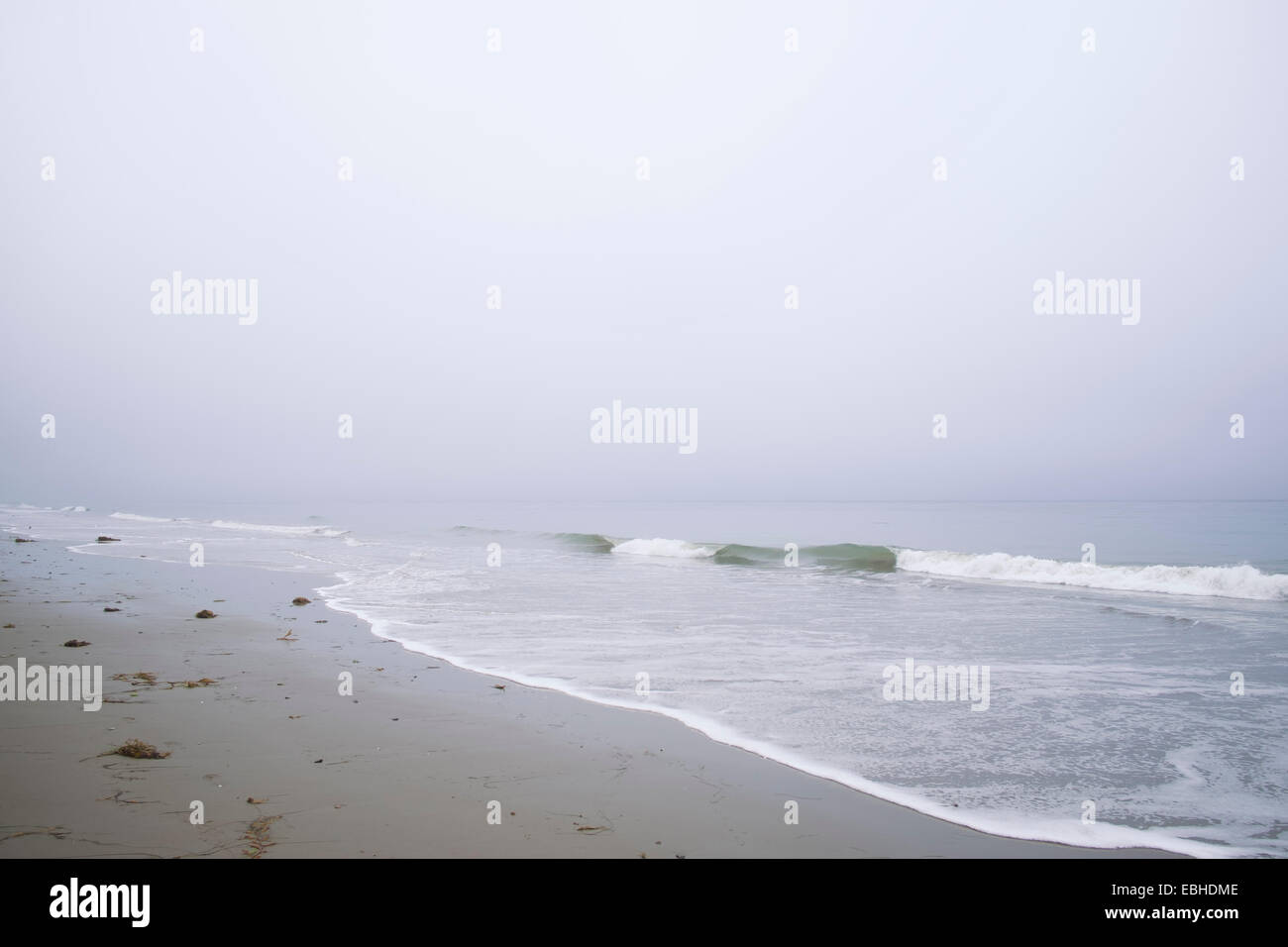 Waves lapping on sandy beach - Stock Image