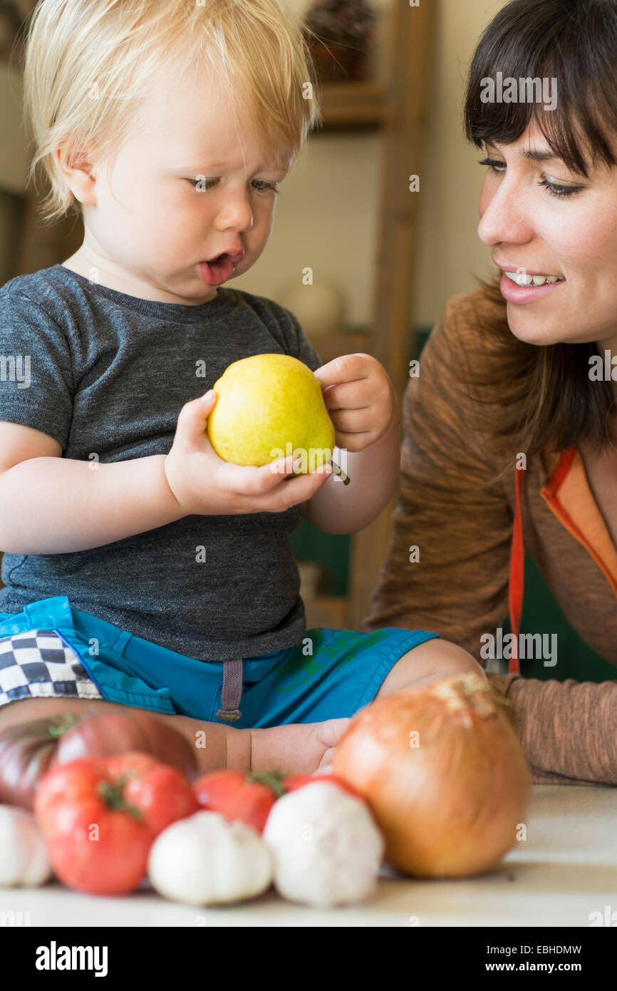 Young boy holding pear with mother - Stock Image