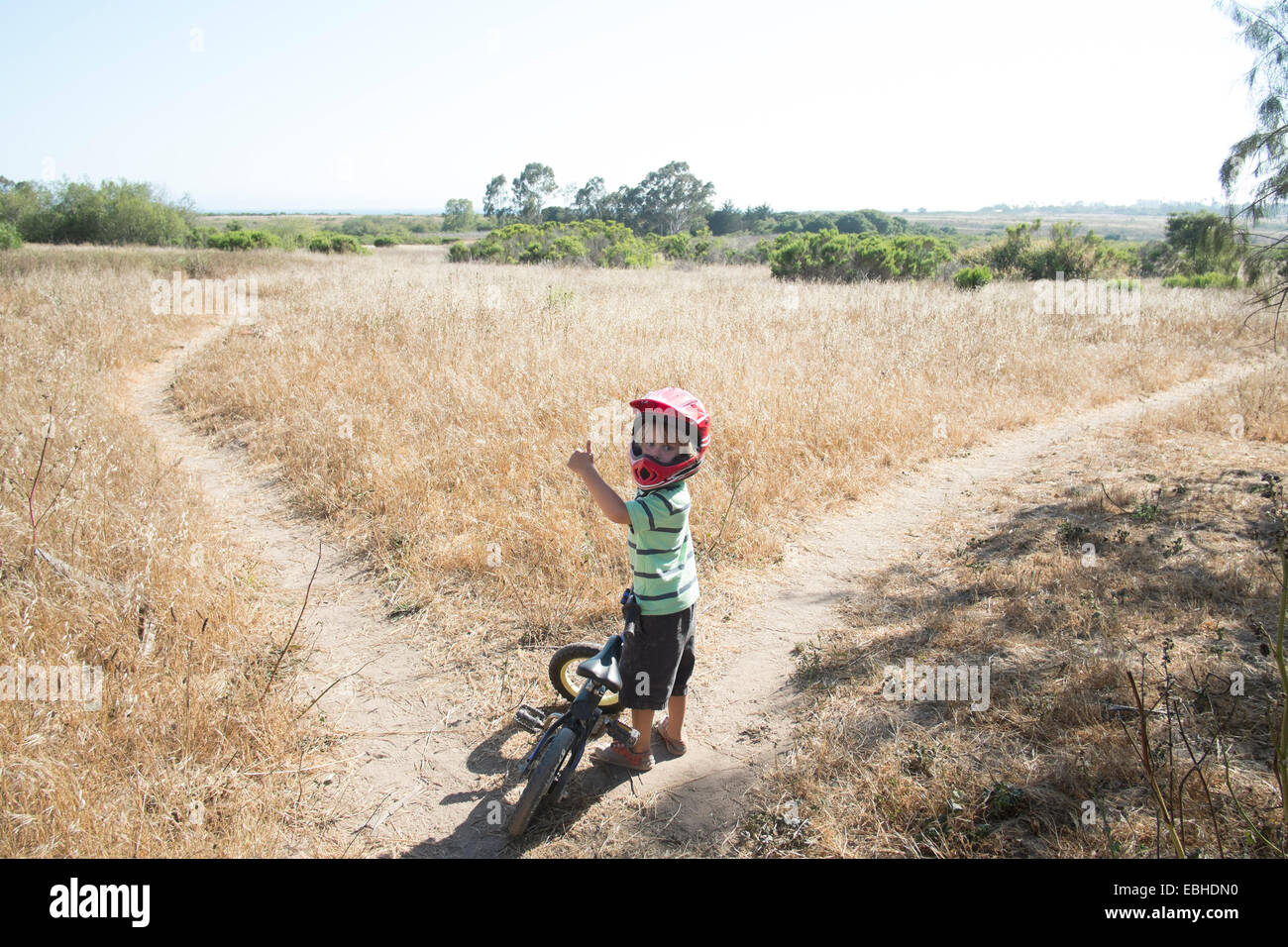 Young boy on path in field with bike - Stock Image