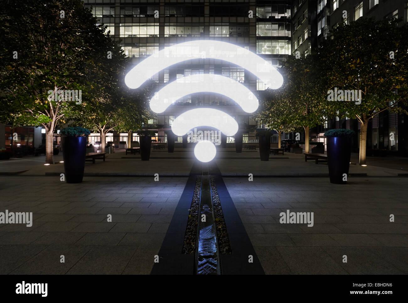Glowing wifi icon in city street at night, London, UK - Stock Image