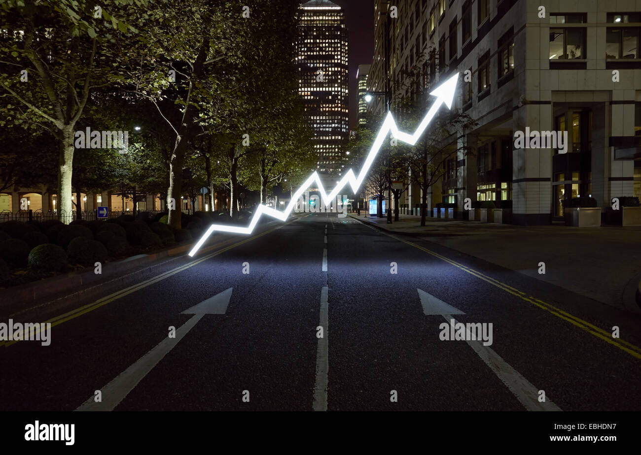Glowing arrow symbol in city street at night, London, UK - Stock Image