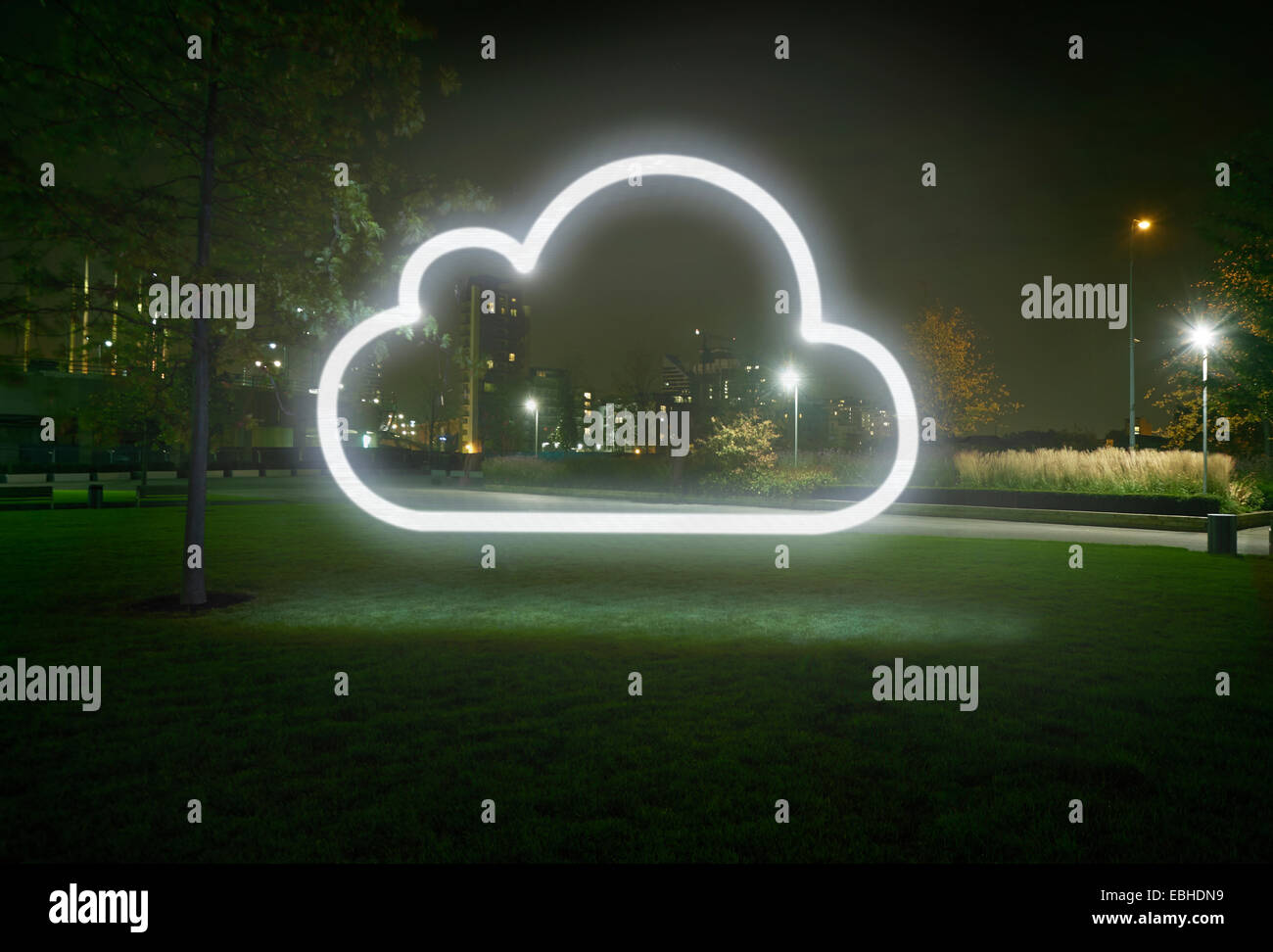 Glowing cloud symbol in city park at night - Stock Image