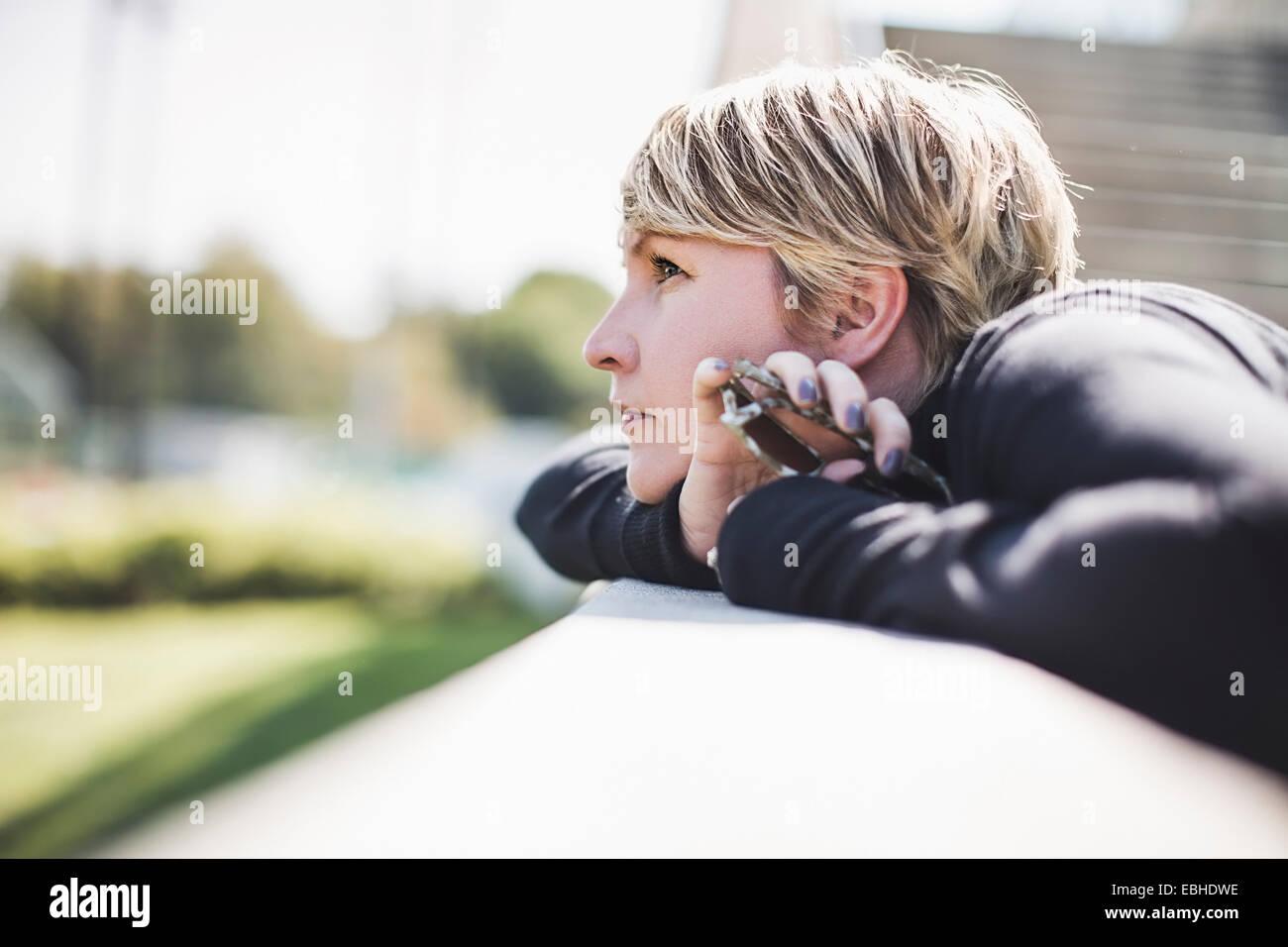 Mature woman gazing from footbridge wall holding onto smartphone - Stock Image