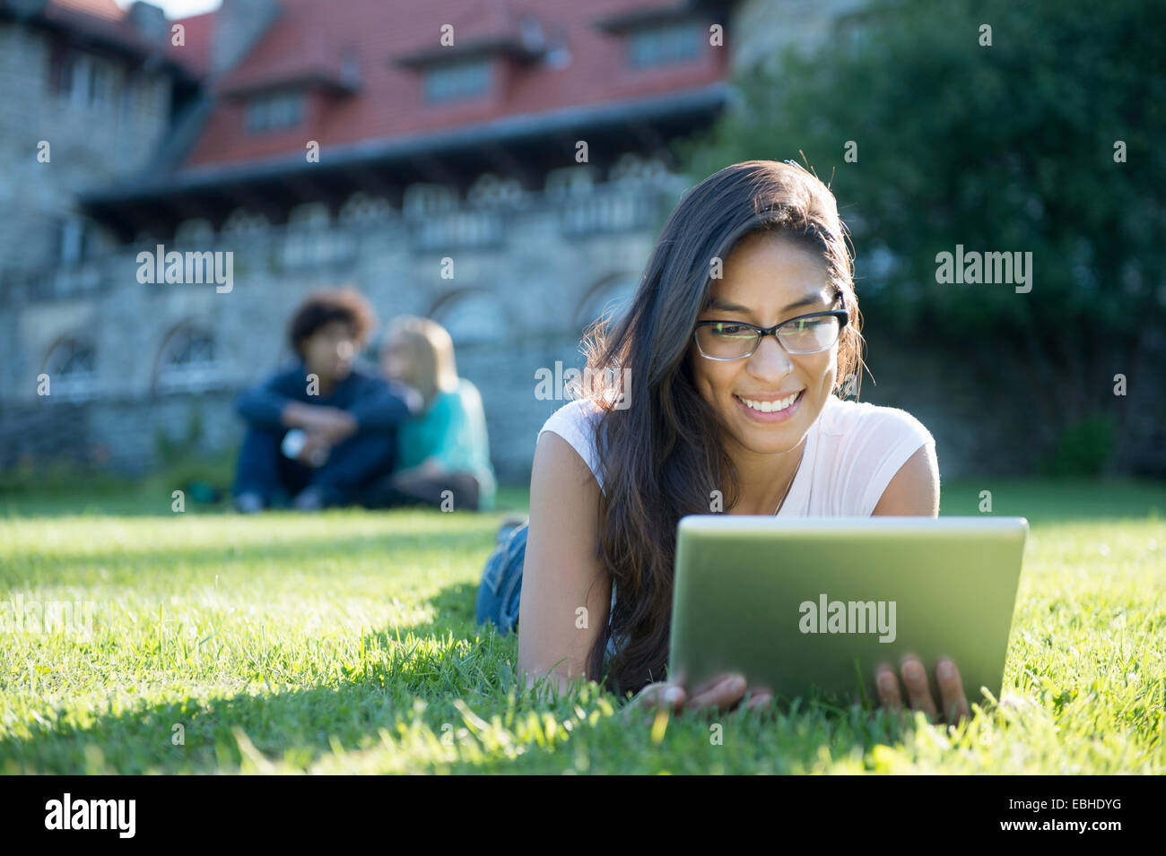 Young woman lying on grass using digital tablet - Stock Image