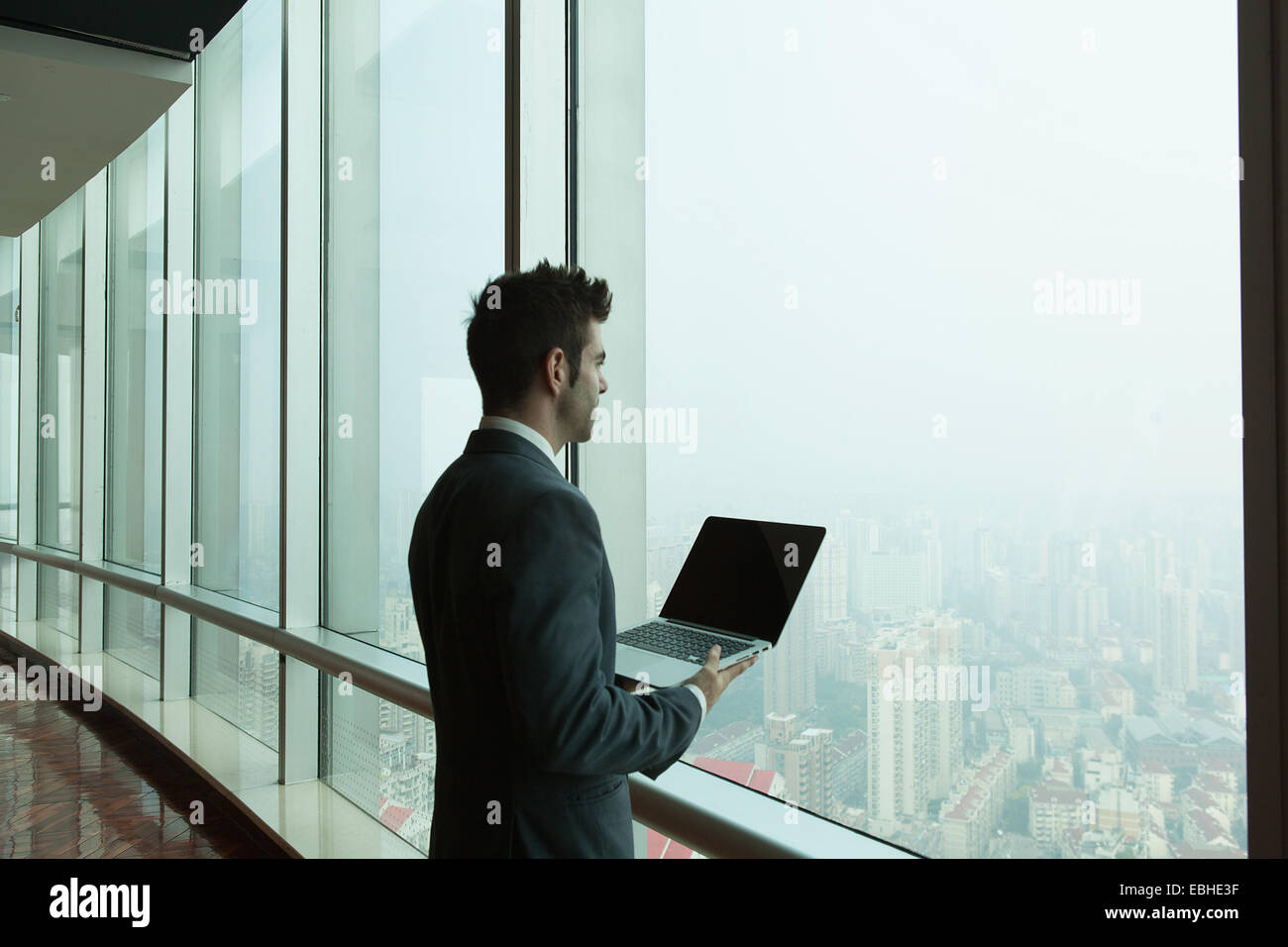 Young businessman with laptop looking out of skyscraper office window, Shanghai, China - Stock Image