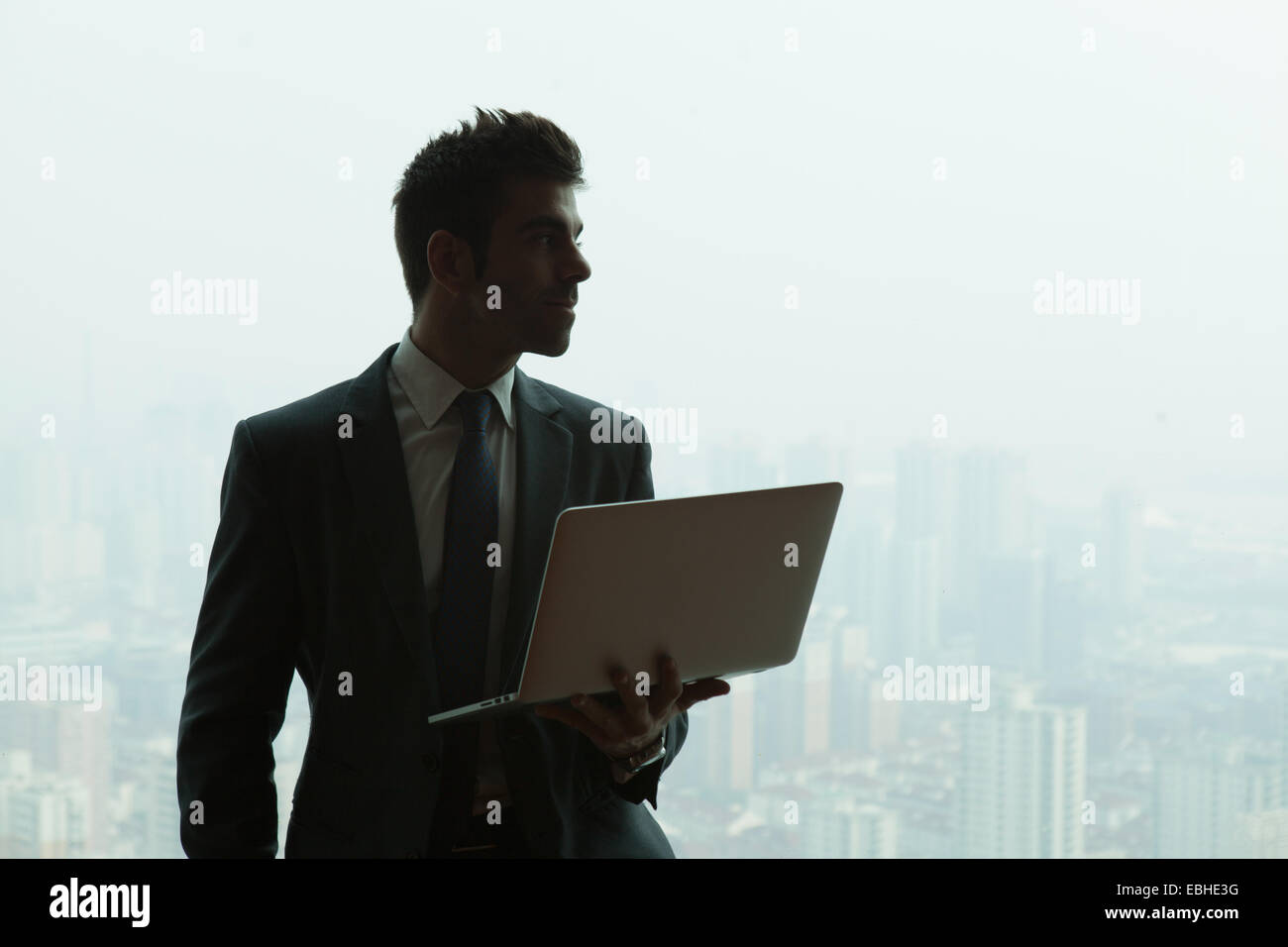 Young businessman with laptop in front of skyscraper office window, Shanghai, China Stock Photo