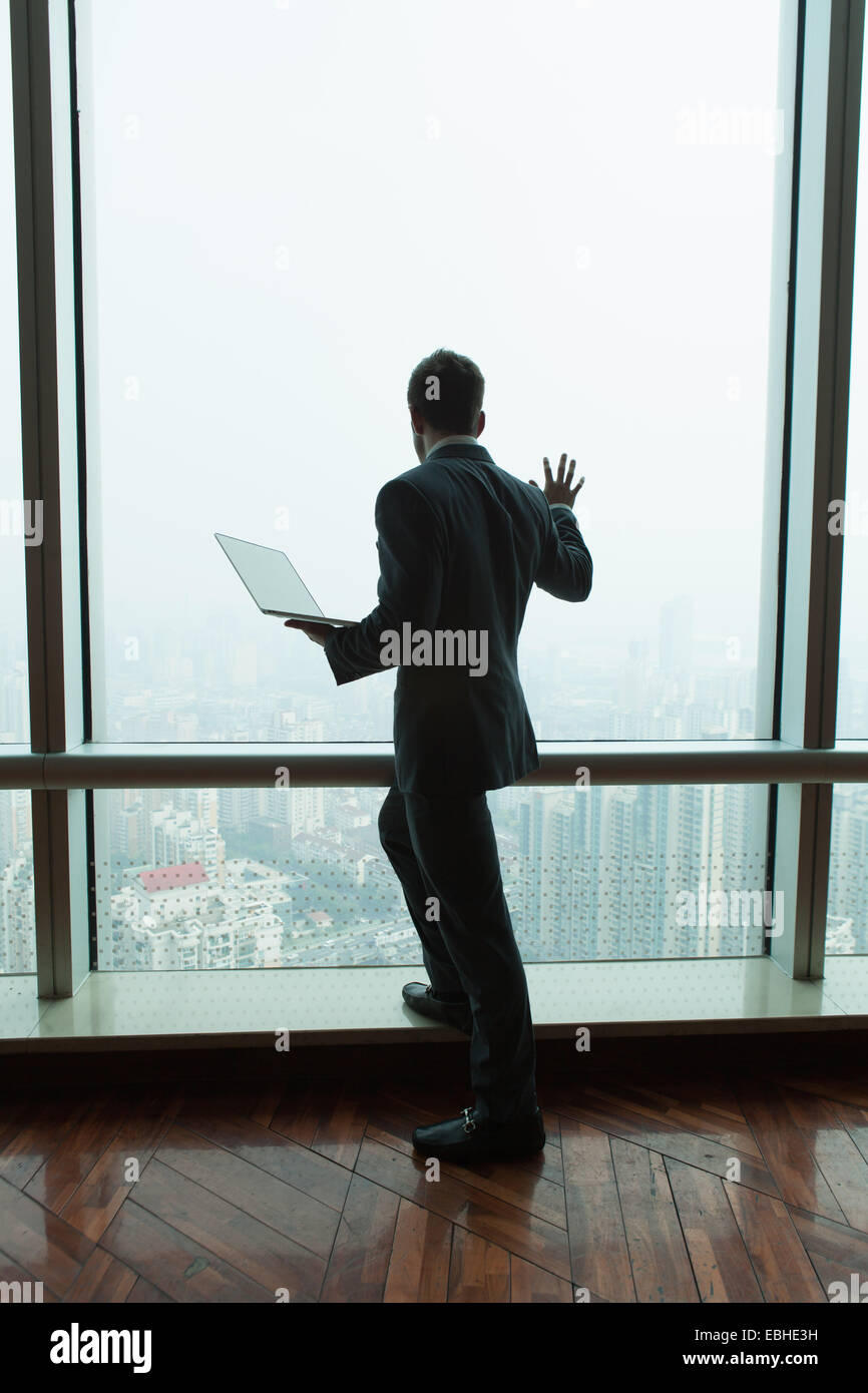 Young businessman with laptop looking down from skyscraper office window, Shanghai, China Stock Photo