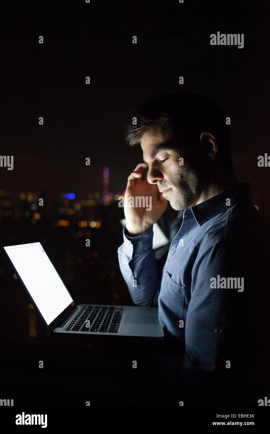 Tired young businessman with laptop in front of skyscraper office window at night, Shanghai, China - Stock Image