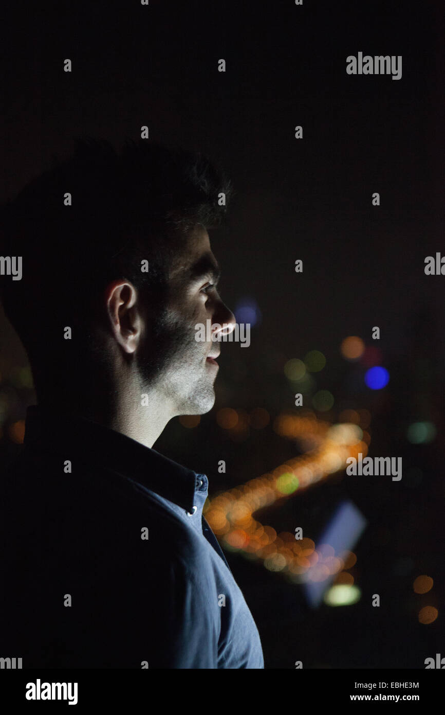 Close up of young businessman looking out of skyscraper office window at night, Shanghai, China - Stock Image