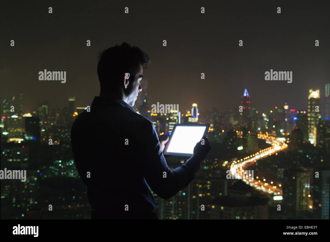 Silhouetted young businessman looking at digital tablet in front of skyscraper office window at night, Shanghai, - Stock Image