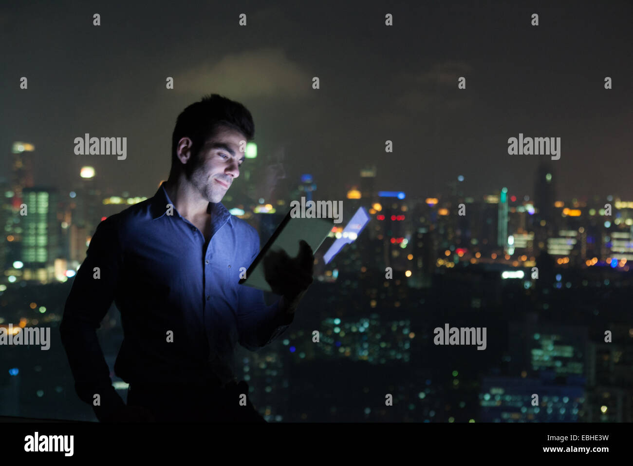 Young businessman looking at digital tablet in front of skyscraper office window at night, Shanghai, China - Stock Image