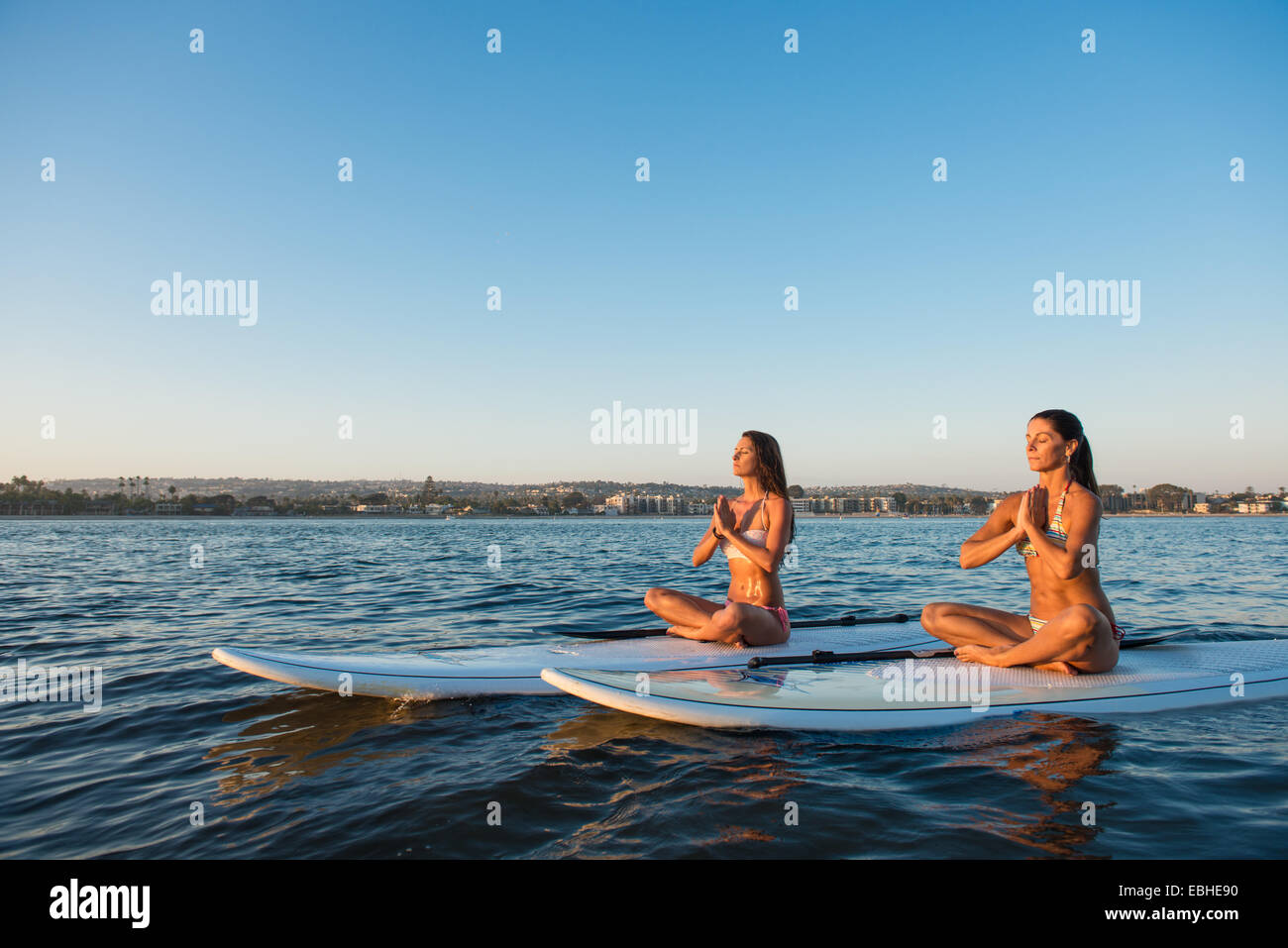 Two women in lotus position on paddleboards, Mission Bay, San Diego, California, USA - Stock Image