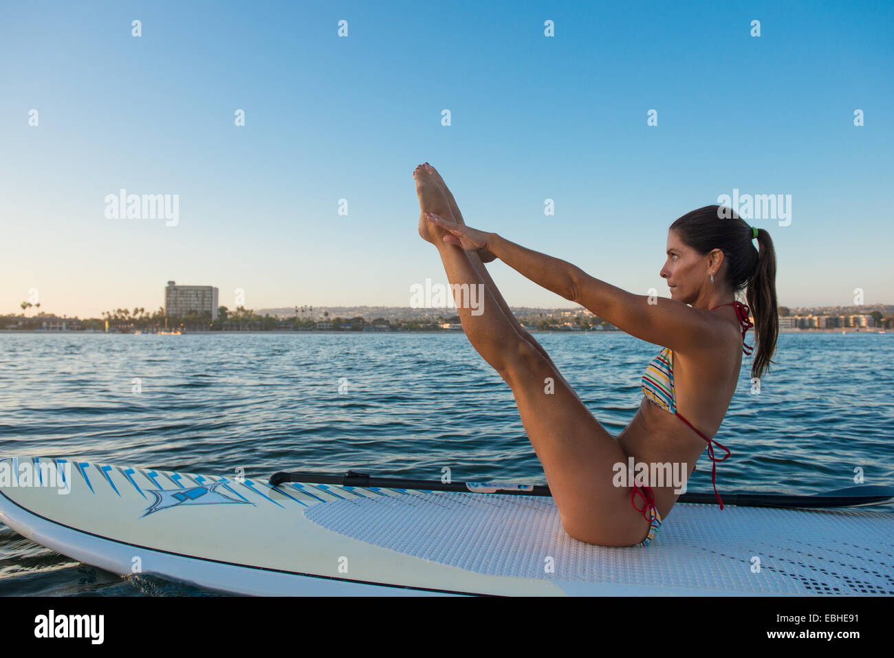 Mature woman in yoga position on paddleboard, Mission Bay, San Diego, California, USA - Stock Image