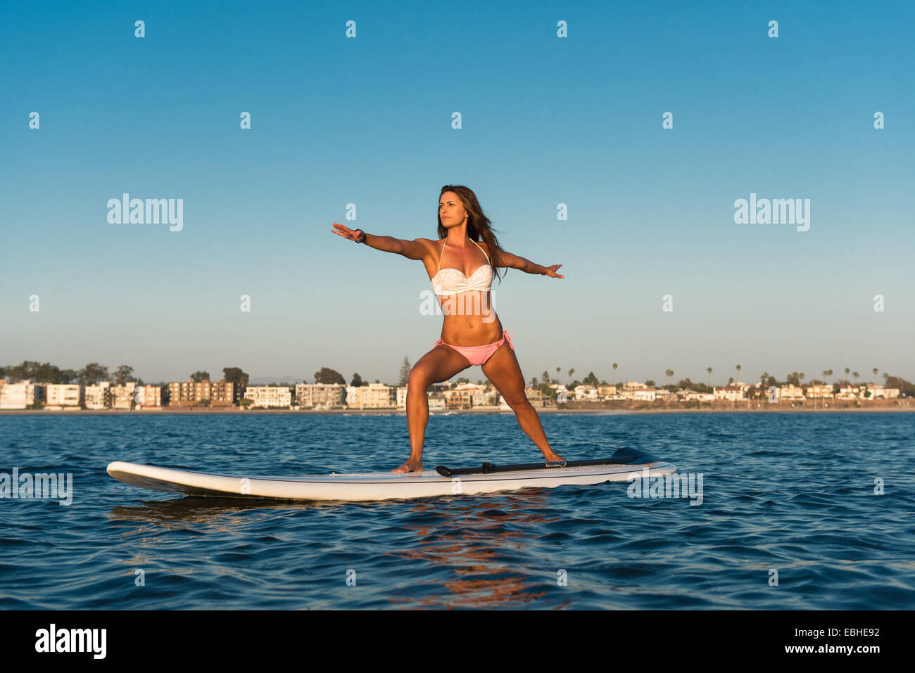 Young woman practicing yoga position on paddleboard, Mission Bay, San Diego, California, USA - Stock Image