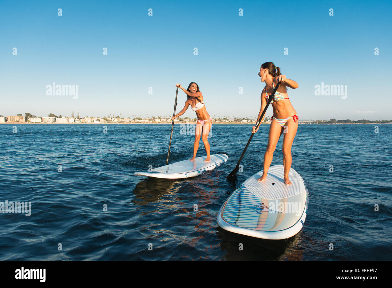 Two women chatting whilst stand up paddleboarding, Mission Bay, San Diego, California, USA - Stock Image