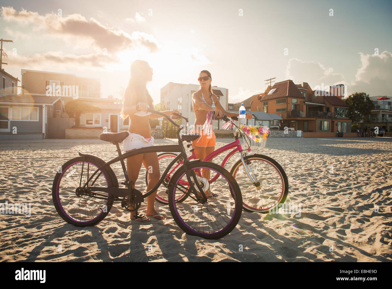 Two women cyclists chatting on beach, Mission Bay, San Diego, California, USA - Stock Image