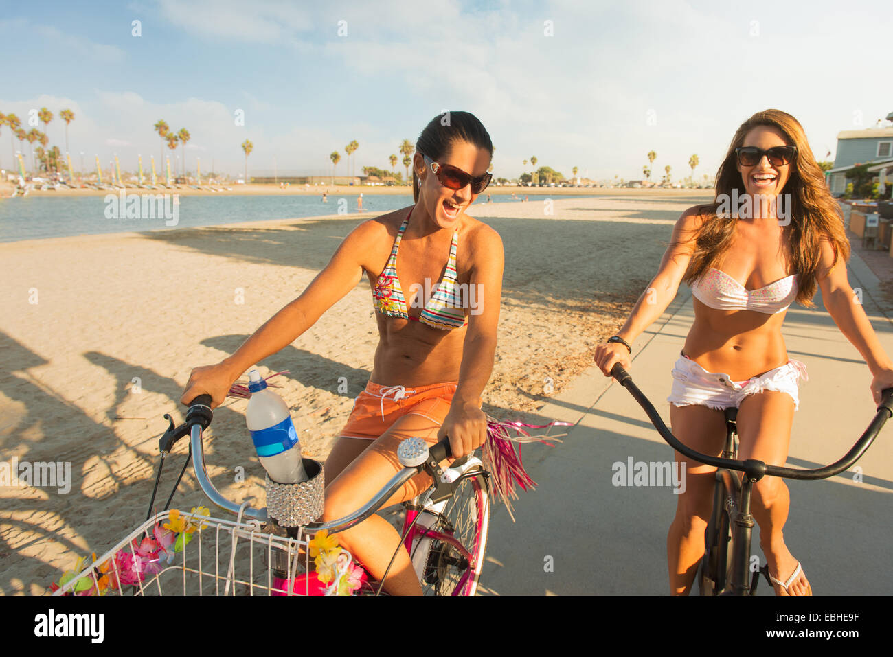 Two women cycling on beach, Mission Bay, San Diego, California, USA - Stock Image