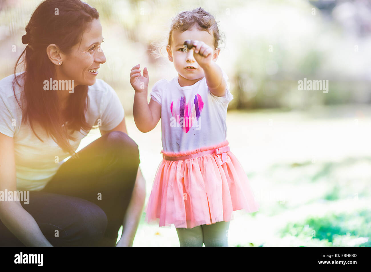 Mother and daughter playing in garden - Stock Image