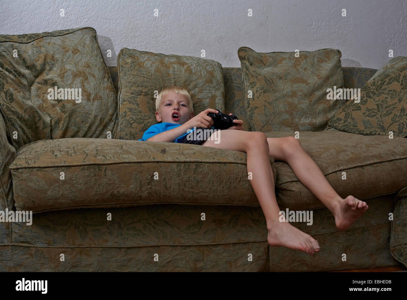 Boy playing video game in living room - Stock Image