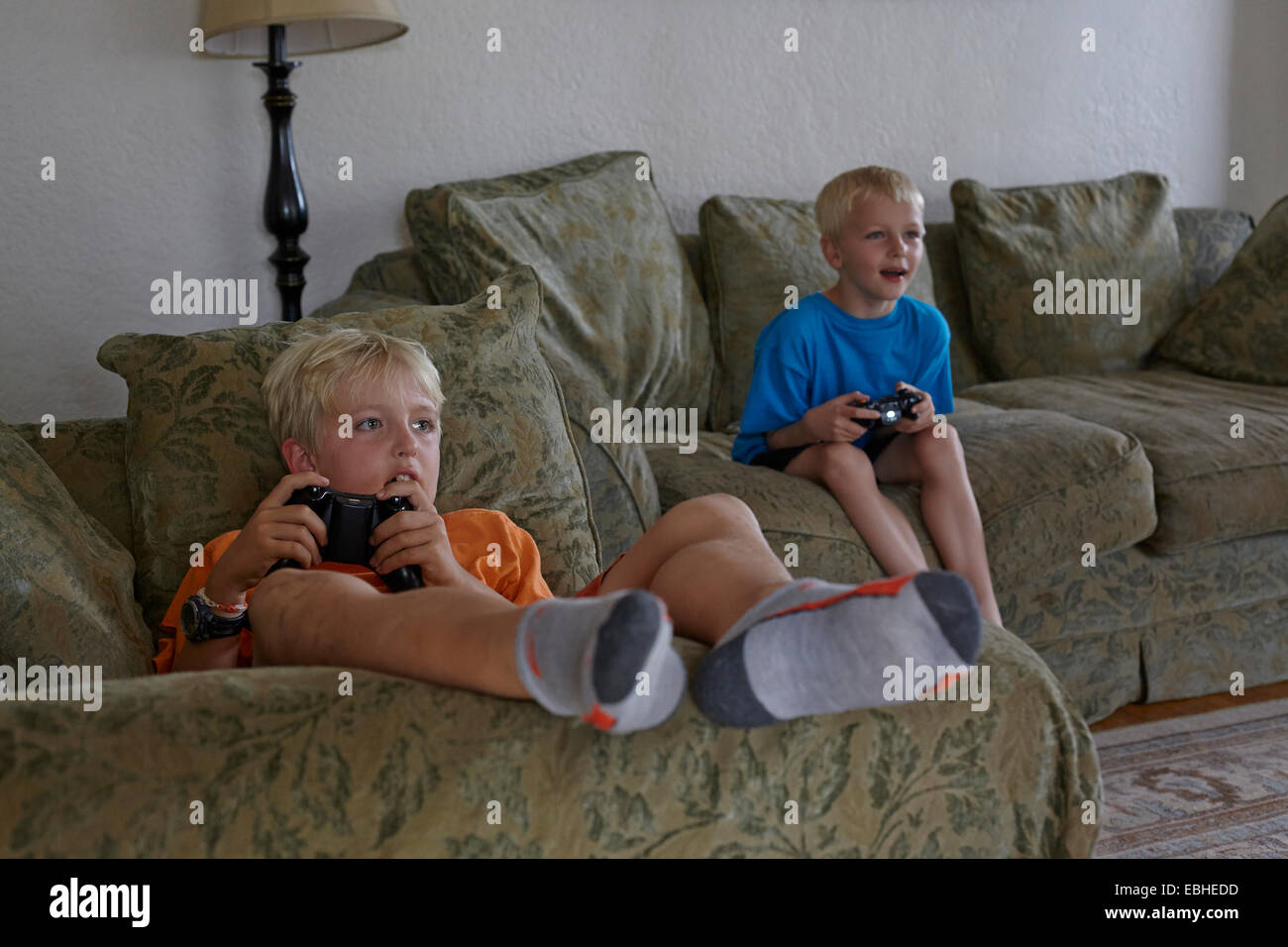 Brothers playing video game in living room - Stock Image