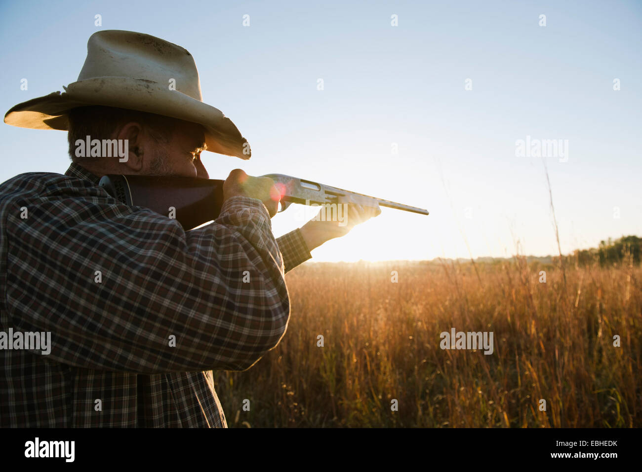 Senior male farmer aiming shotgun in remote field at dusk, Plattsburg, Missouri, USA - Stock Image