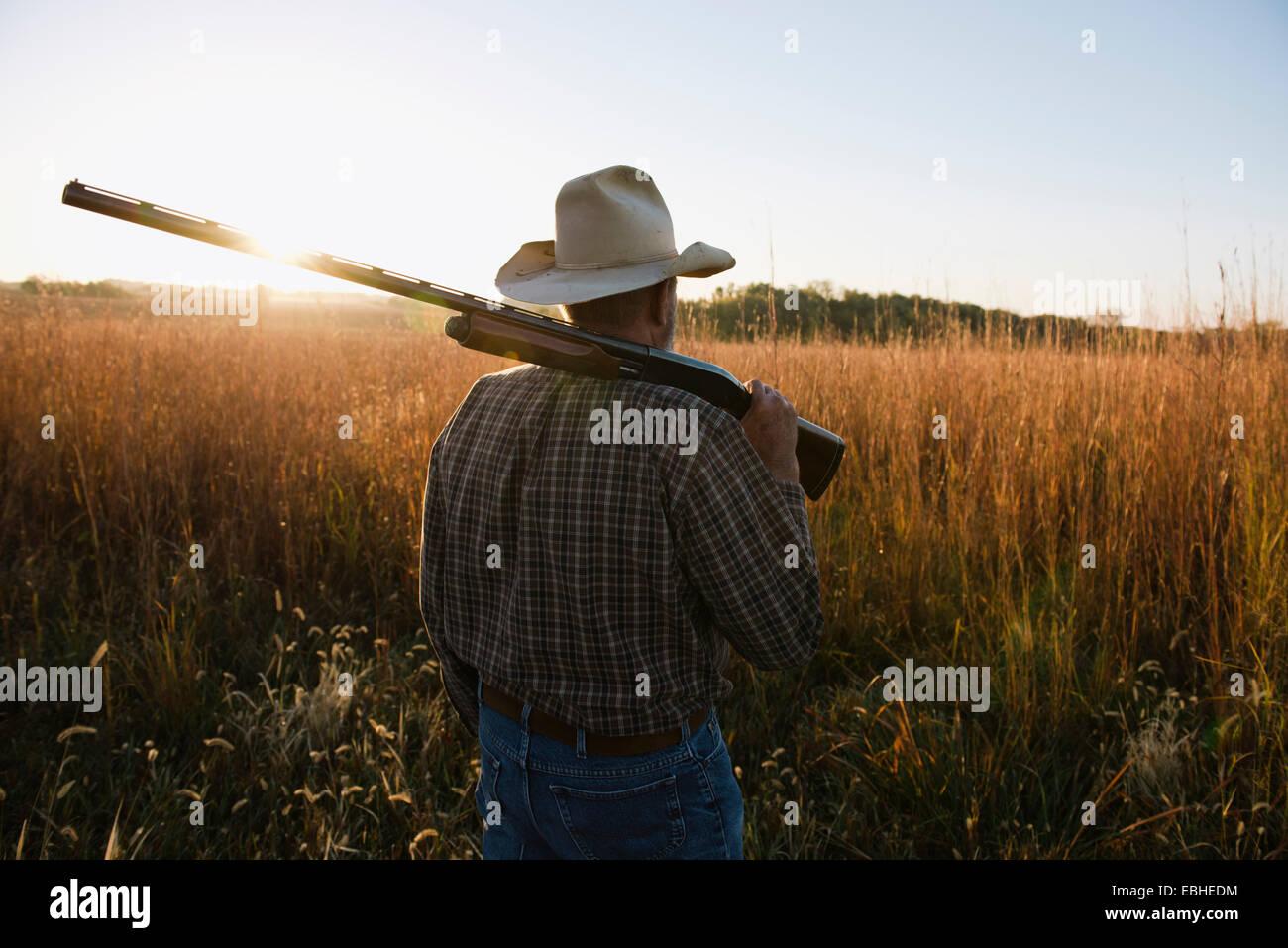 Senior male farmer with shotgun on shoulder in remote field at dusk, Plattsburg, Missouri, USA - Stock Image