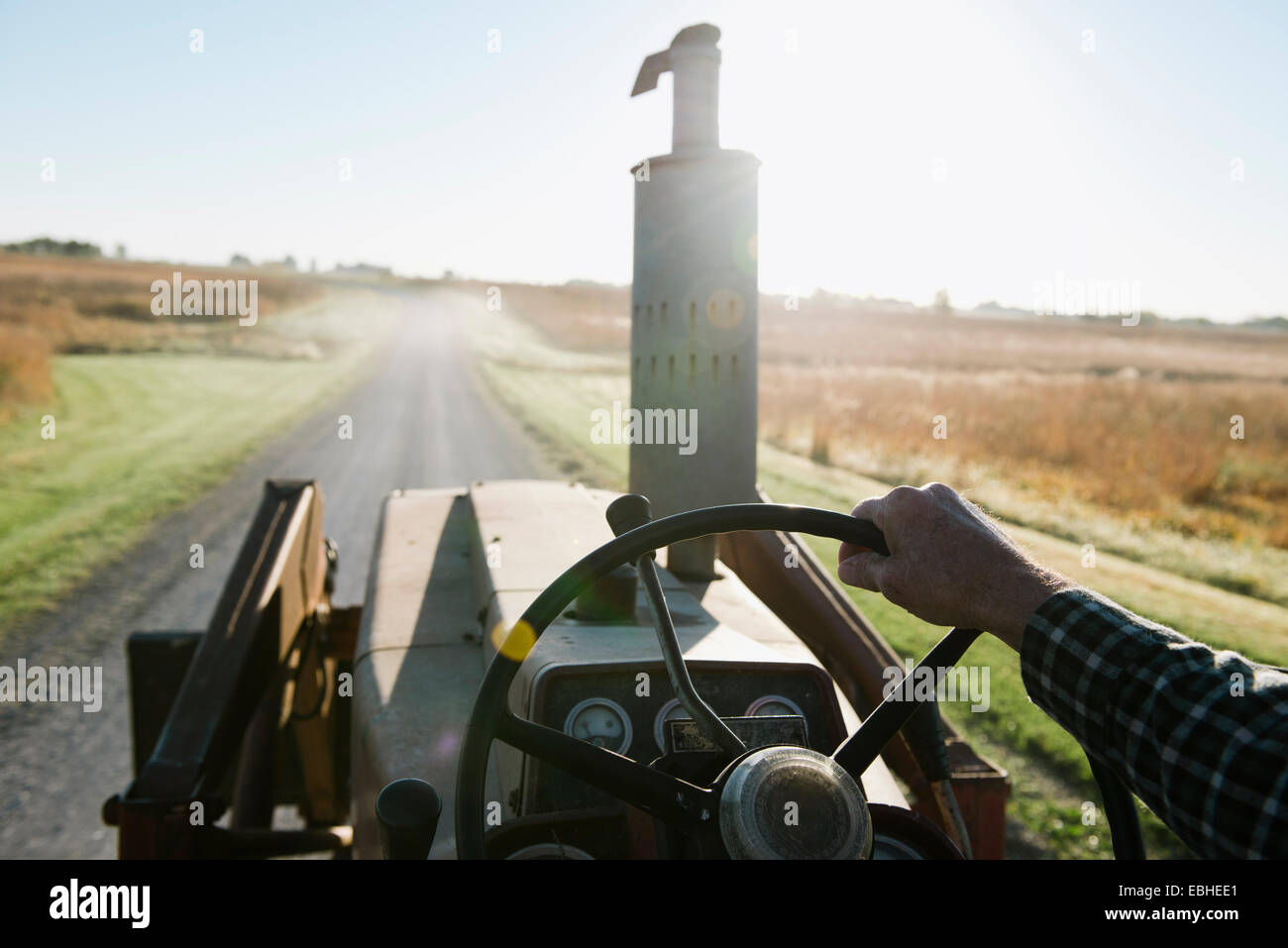 Over shoulder view of senior male farmer driving tractor on rural road, Plattsburg, Missouri, USA - Stock Image