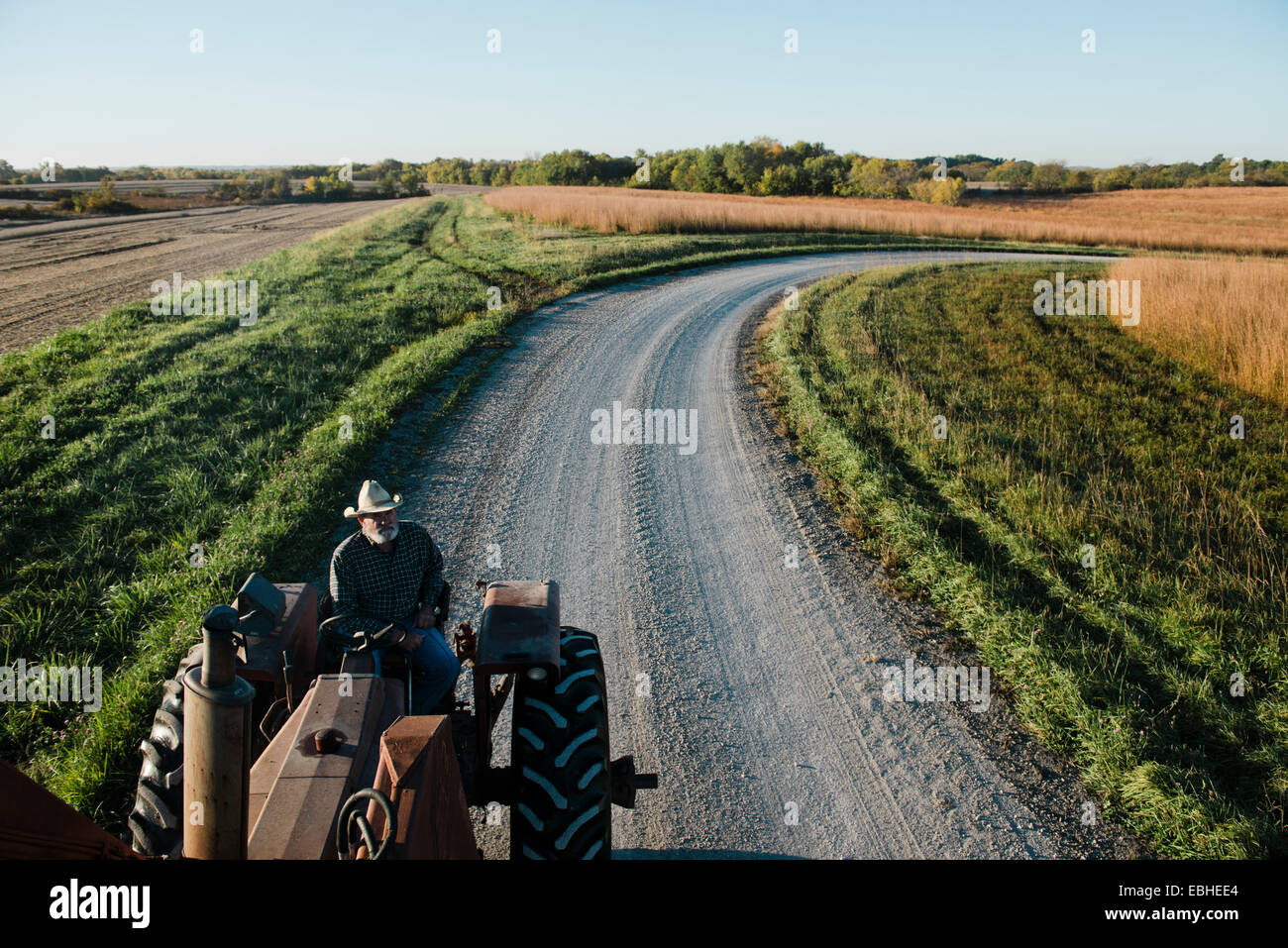 High angle view of senior male farmer driving tractor on rural road, Plattsburg, Missouri, USA - Stock Image