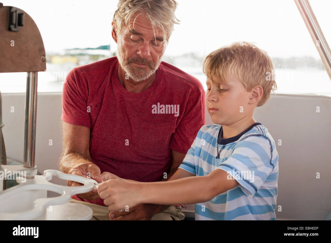 Grandfather teaching grandson to tie knots on sailboat - Stock Image