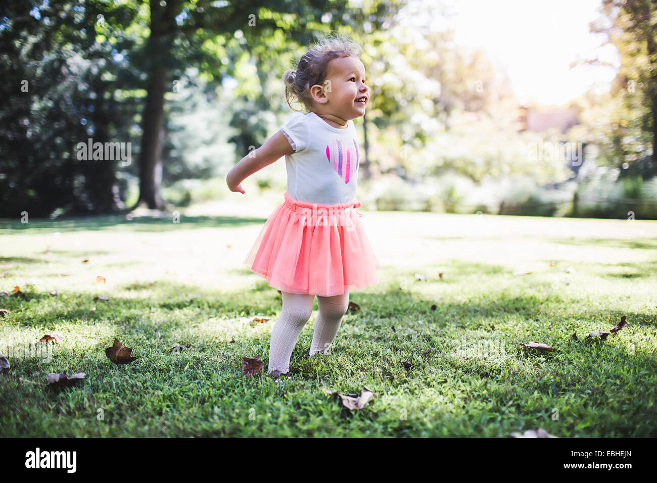 Baby girl playing in garden - Stock Image