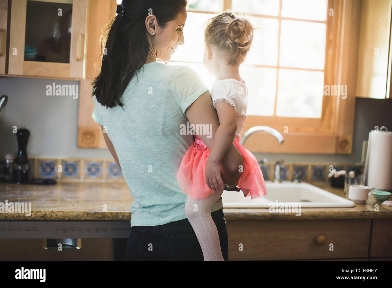 Mother and daughter playing in kitchen - Stock Image