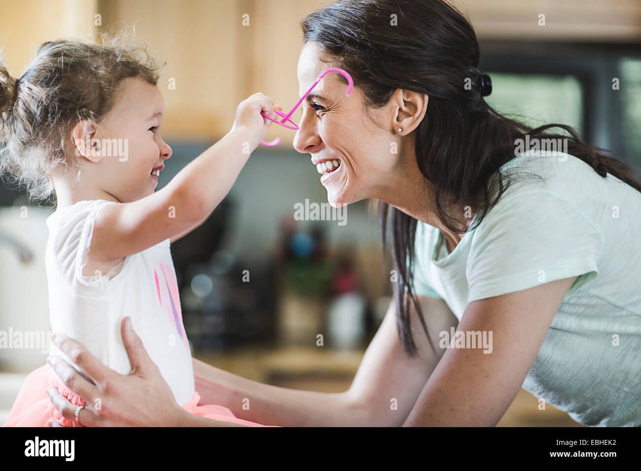 Mother and daughter playing in kitchen Stock Photo